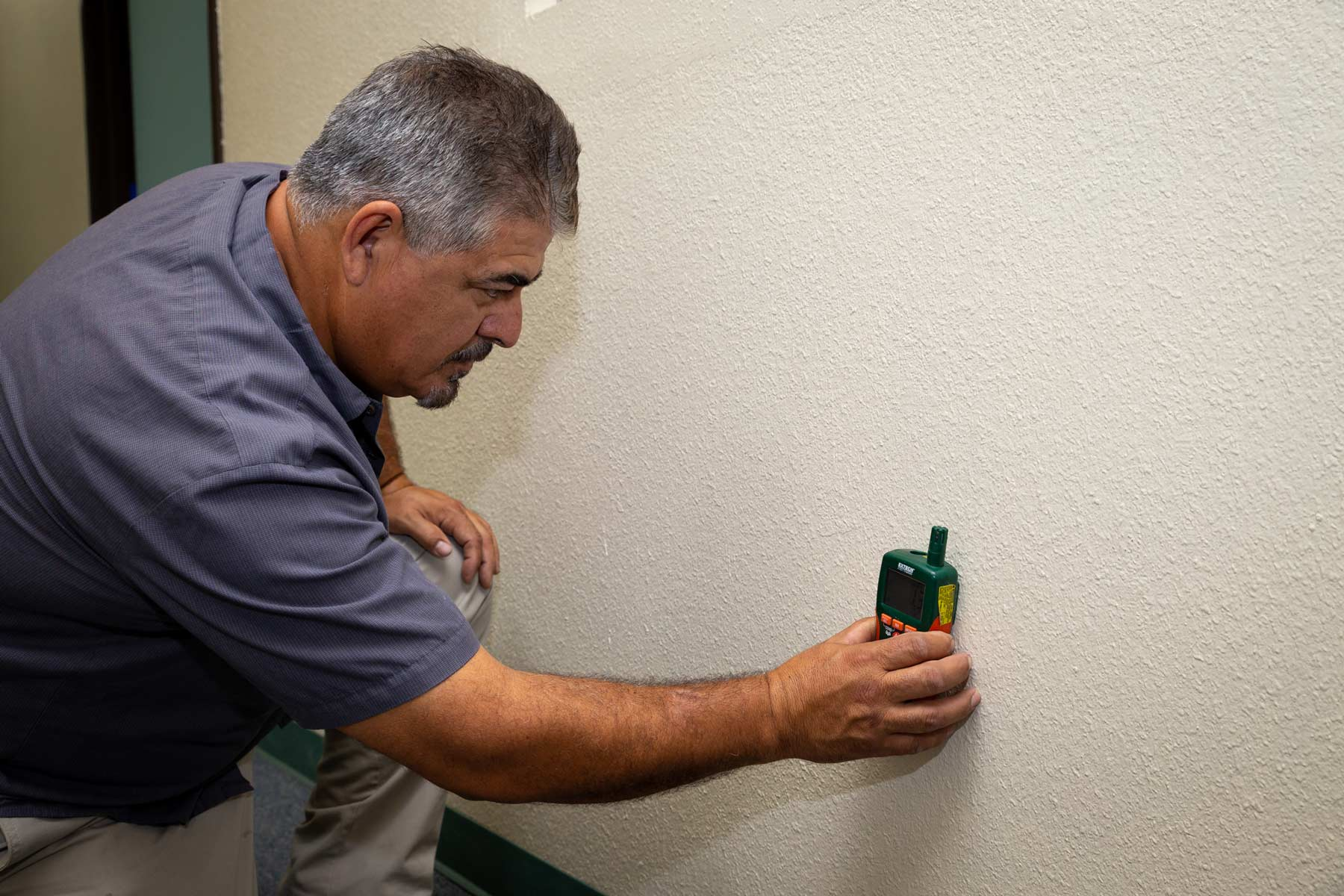 Experienced water damage restoration technician testing wall for moisture