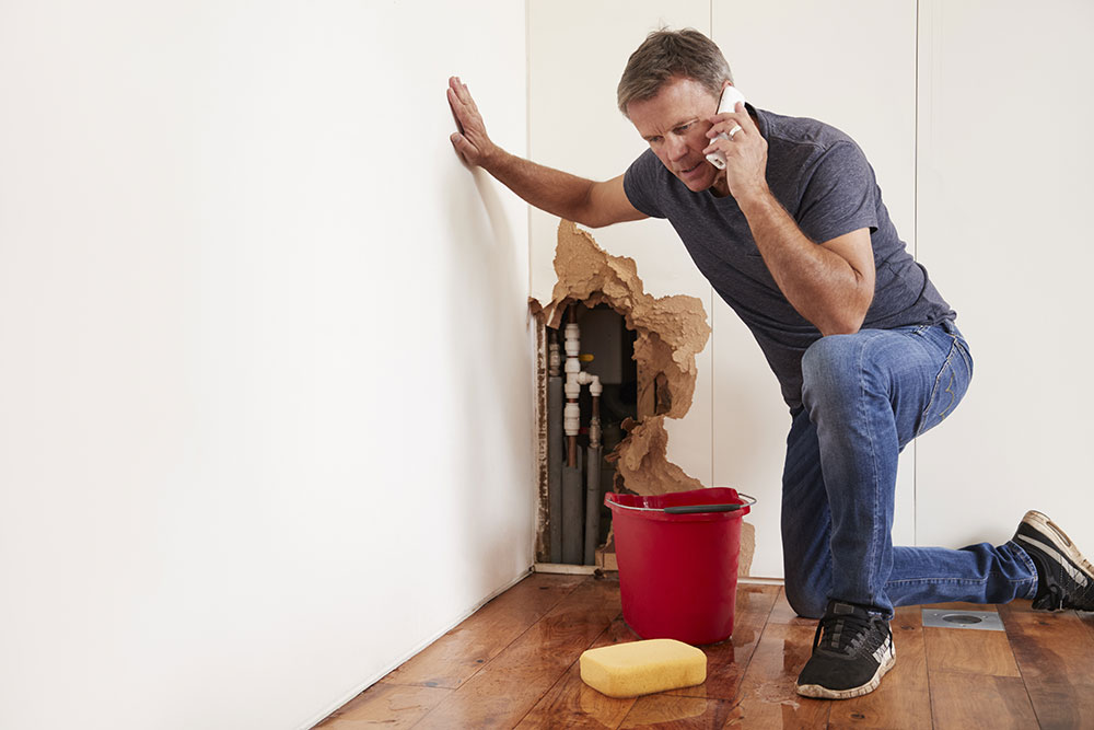 man with burst water pipe